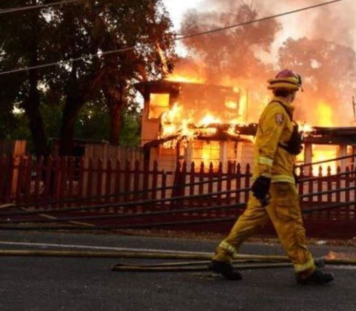 A Fire fighter walking in front of a burning home